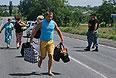 Жители Донецкой области идут по дороге из Шахтерска.