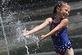 Девочка купается в фонтане на Крымской набережной.