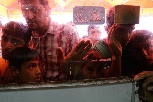 Жители Газы всматриваются в окна микроавтобуса в поисках раненых и убитых родственников.