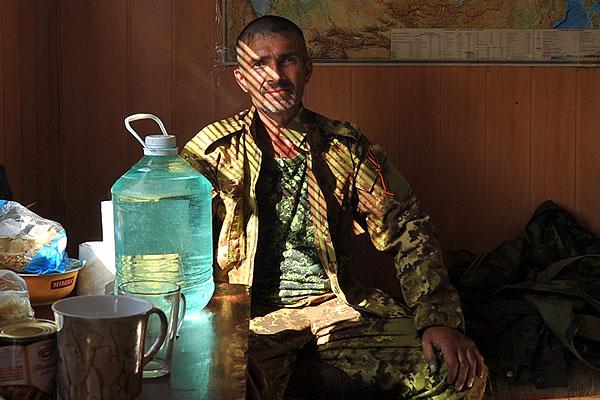 Народный ополченец, контролирующий подъезд на границе.