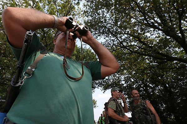 Ополченцы ДНР осматривают поле, на котором ведутся поисковые работы.
