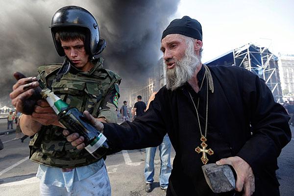 Бутылка с зажигательной смесью в руках священника.