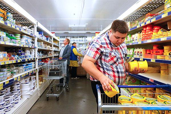 Сотрудник магазина выкладывает на полки продукцию компании Valio.