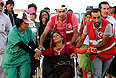 Сотрудники курдского отделения Красного Полумесяца помогают женщине на инвалидном кресле.