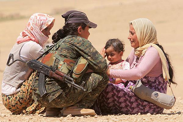 Женщина из отряда помощи курдам утешает женщин с маленьким ребенком.