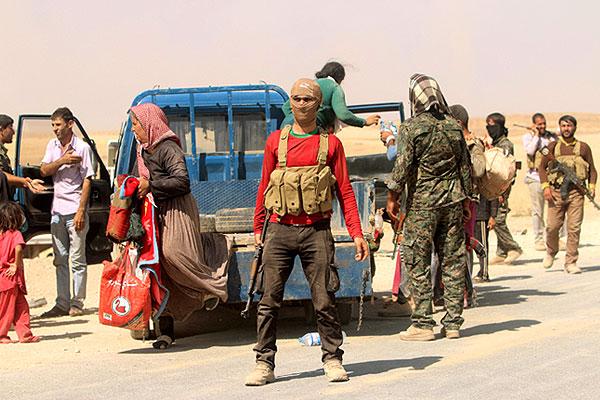 Солдаты курдской армии помогают беженцам в пути.