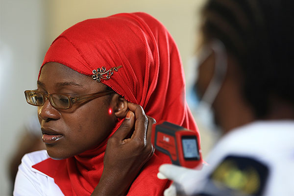 Сотрудница миграционного контроля в нигерийском аэропорту измеряет лазерным термометром температуру тела прибывшей пассажирки.