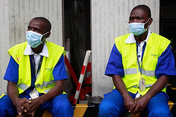 Сотрудники службы безопасности аэропорта Абиджана. Кот-д'Ивуар закрыл авиасообщение с Либерией, Гвинеей и Сиерра-Леоне из-за вспышки лихорадки Эбола.