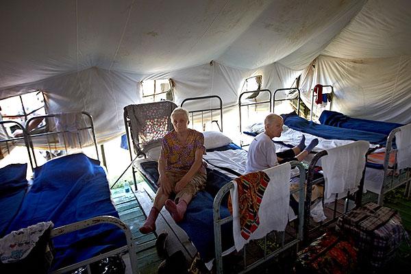 Пожилые женщины отдыхают в палатках.
