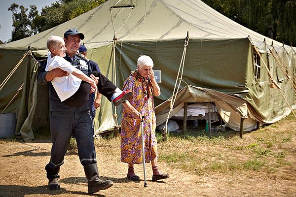 Сотрудник МЧС Украины несет на руках пожилую женщину.