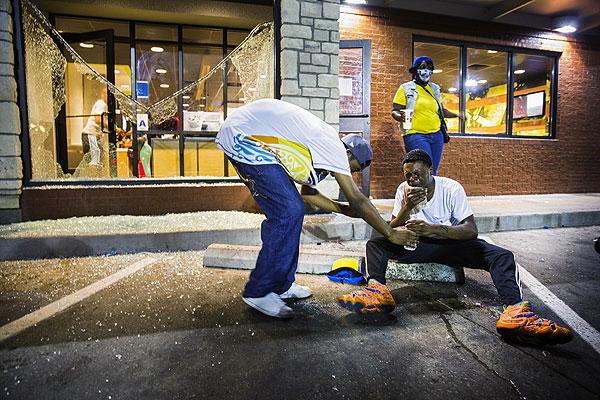 Жители города смывают слезоточивый газ.