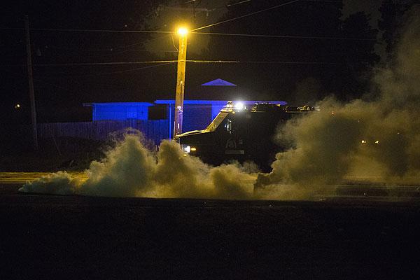 Бронированный автомобиль полиции в клубах слезоточивого газа.