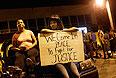 Жительницы Фергюсона, принимающие участие в демонстрации, сидят с плакатом на капоте автомобиля.