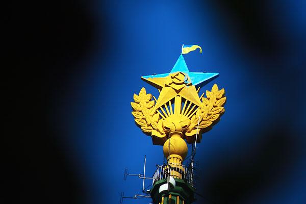 Звезда, раскрашенная в цвета флага Украины и флаг Украины, вывешенный на жилом доме на Котельнической набережной.