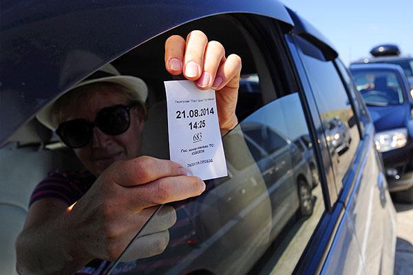 """Водитель демонстрирует талон с порядковым номером, в котором указано время заезда и номер автомобиля, переправляющегося через Керченскую переправу, на накопительной площадке у аэропорта """"Керчь""""."""