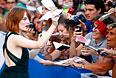 Актриса Эмма Стоун раздает автографы на красной ковровой дорожке.