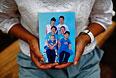 """Семейное фото в руках женщины, чей муж был на борту пропавшего """"Боинга""""."""