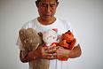 Мужчина держит плюшевые игрушки своей дочери, которая была на борту MH370.