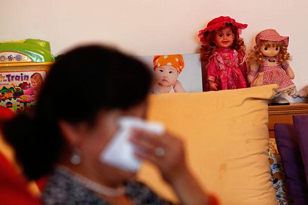 Женщина плачет в пустой гостиной своего дома. На борту пропавшего лайнера был ее сын со своей семьей.