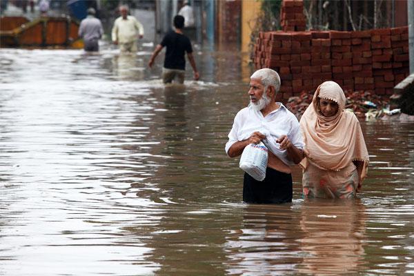 Пожилая пара пересекает затопленную дорогу в Лахоре. Пакистан.