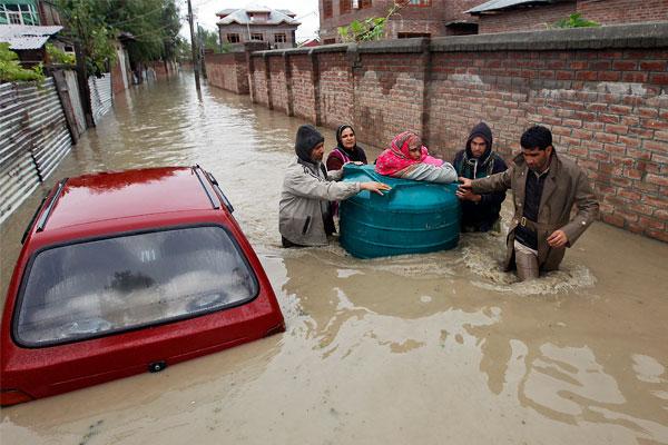 Индийцы помогают больной женщине переправиться через затопленную улицу.