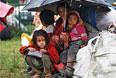 Дети спасаются под зонтиком от дождей в Шринагаре. Индия.