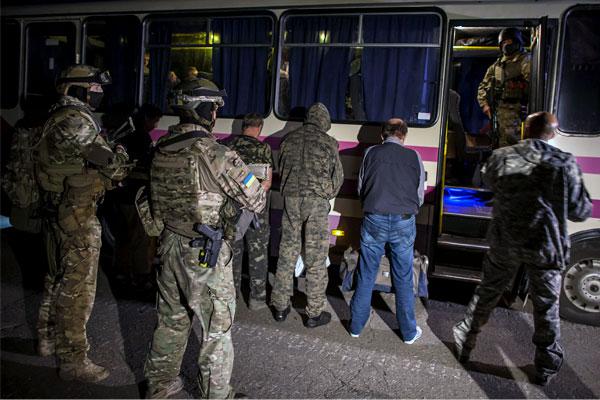 Пленные ополченцы под охраной украинских военных ожидают обмена.