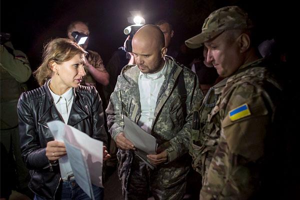 Представители самопровозглашенной ДНР (слева) и  правительства Украины обсуждают процесс обмена пленными.