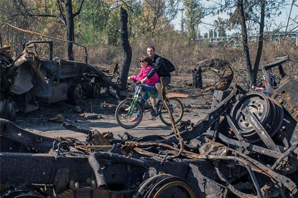Молодая пара проезжает на велосипеде мимо сгоревших танков и автомобилей.