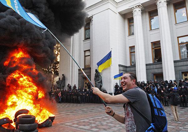 """Участники акции держали флаги партий """"Правый сектор"""", """"Воля"""", ВО """"Свобода"""", государственные флаги Украины, символику Автомайдана, а также плакаты с требованиями люстрации власти."""