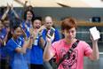Работники магазина аплодируют одному из первых покупателей нового iPhone 6 в Токио.