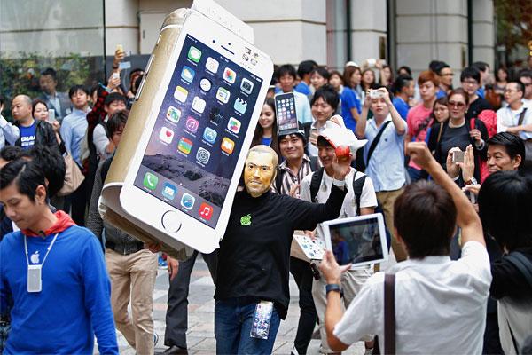 Мужчина в маске Стива Джобса держит картонную копию нового смартфона в первый день продаж iPhone 6 в Токио.