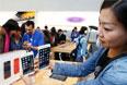Покупательница демонстрирует новинки компании Apple в Токио.