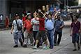 Выступающие против разного рода оккупаев жители города мешают работе фотографа, снимающего продемократических протестующих.