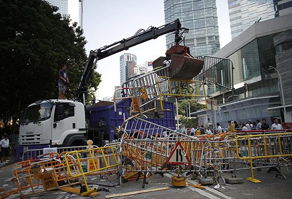 Кран убирает баррикады возле адмиралтейства в Гонконге.