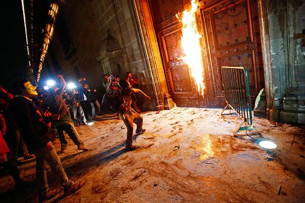 Участники акции протеста поджигают дверь Национального дворца - резиденции президента Мексики Энрике Пенья Ньето.