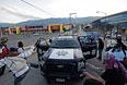 Протестующие студенты атакуют полицейскую машину.