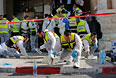 Добровольцы израильской общественной организации ЗАКА отмывают кровь на месте нападения.