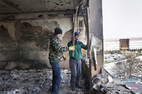 Рабочие проводят уборку разрушенного в ходе спецоперации здания