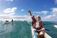 Дональд Бойс, переодетый в Санта-Клауса, рассекает волны в каное у пляжа Ваикики в Гонолулу, Гавайи