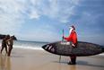 Бразильский серфер Карлос Байя в костюме Санта-Клауса беседует с мальчиками на пляже в Сан-Паулу