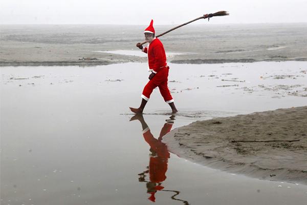 Индийский мужчина в костюме Санта-Клауса после очистки берегов реки Ганг в городе Аллахабад