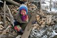 Пожилая женщина у разрушенного в результате боевых действий дома в Горловке, 10 февраля