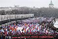 """Участники акции несут большое количество фотографий застреленного Б.Немцова, также в колонне сотни российских флагов с траурными лентами, флаги движения """"Солидарность"""" и транспаранты с различными лозунгами."""