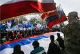 Участники торжественного митинга разворачивают 18-метровый триколор, подписанный крымчанами год назад, после референдума о присоединении к России