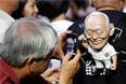 """Сторонник партии """"Народное действие"""" фотографирует фигуру Ли Куан Ю во время предвыборного митинга в Сингапуре, май 2011 год"""