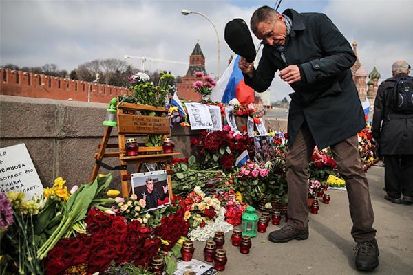 Житель города во время возложения цветов на Большом Москворецком мосту