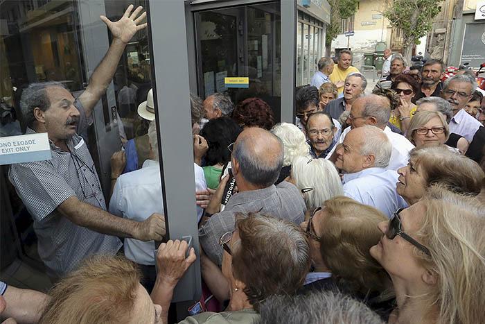 """Министр финансов Греции Янис Варуфакис в интервью Bloomberg TV в четверг пообещал уйти в отставку, если на воскресном референдуме его соотечественники скажут """"да"""" в ответ на требования международных кредиторов. На фото: пожилые люди, пришедшие за частью своей пенсии у отделения банка на острове Крит."""