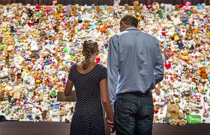 Члены семьи и друзья погибших у стены из тысячи мягких игрушек, собранных в голландском городе Ньювегейн в память о жертвах авиакатастрофы