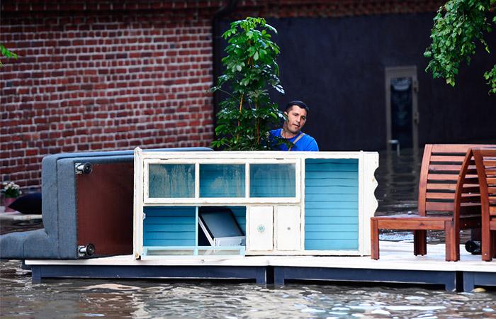 Мужчина перевозит уцелевшие вещи из дома, затопленного в результате наводнения